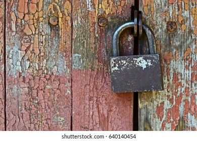 Old metal padlock on a wooden door