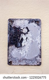 """Old metal plate with sign """"For men"""" on a stucco wall. Close up."""