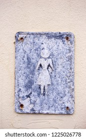 """Old metal plate with sign """"For women"""" on a stucco wall. Close up."""