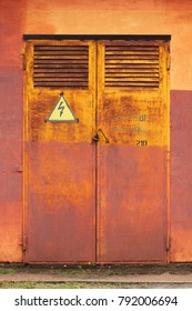 Old metal rusty grunge door to electric switchboard with high voltage arrow lightning sign in yellow triangle, abstract background