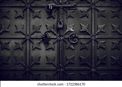 Old metal rusty wrought-iron doors of dark color. Visible rust and scuffs and small details.