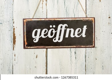 Old metal sign in front of a white wooden wall - German word for Open - geoeffnet