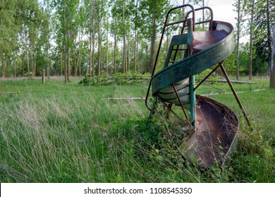 An old metal spiral slide in a now abandoned playground.