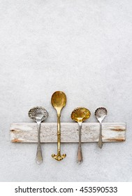 Old metal spoons on concrete background.