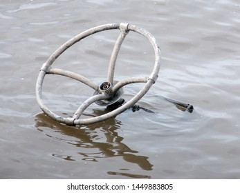 Old metal steering wheel, abandoned and submerged in the Mississippi River