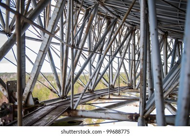 Old metal structure with supporting girders and pipes.