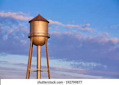 A old metal water tank, in the light of the morning sun, stands tall against a colorful cloudy sky in America's Midwest.