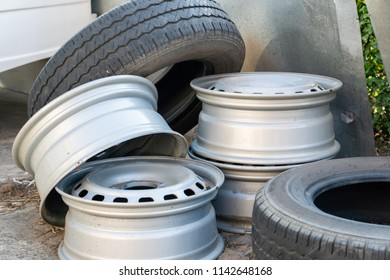 Old metal wheel rims and tires abandon in the car dump, vehicle waste