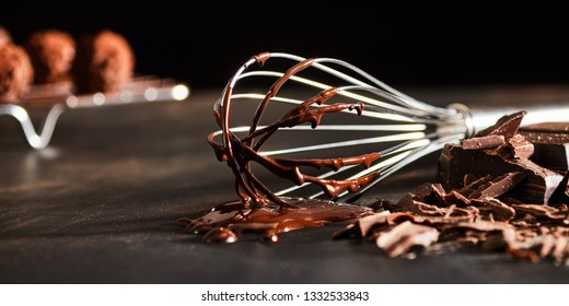 Old metal whisk coated in melted chocolate lying on a kitchen counter alongside chopped chocolate candy in banner format with copy space