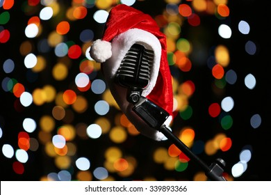 Old microphone decorated with Christmas hat against defocused lights