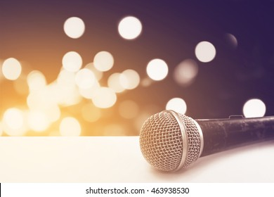 old microphone on white grunge table with blur bokeh from traffic light background in soft focusing
