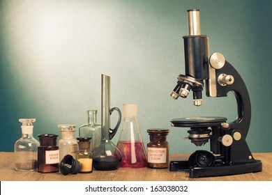 Old microscope and laboratory glass on table