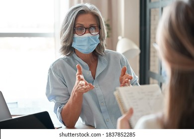 Old middle aged female mentor, teacher, hr manager wearing face mask training young worker intern, teaching student, interviewing job seeker at meeting in office. Social distance and safety at work.