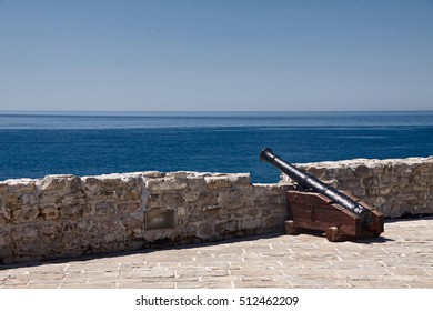 Old miedival cannon on castle wall in front of sea