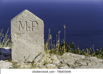 Old milestone with Roman inscription MP (milia passuum) in front of blue sea as background.
