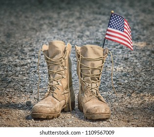 Old military combat boots with the American flag. Rocky gravel background. Memorial Day or Veterans day concept.