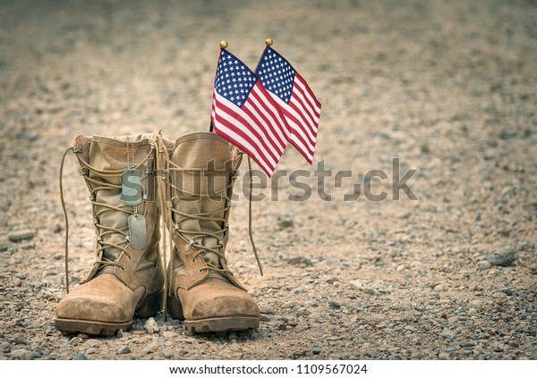 Old military combat boots with dog tags and two small American flags. Rocky gravel background with copy space. Memorial Day or Veterans day concept.