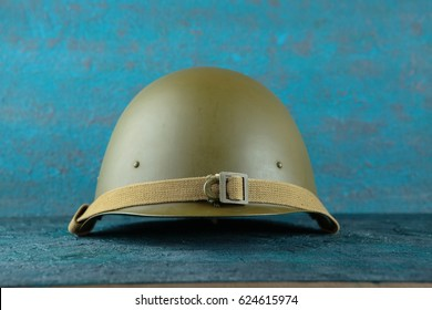 Old military helmet from the Second World War on cement background.