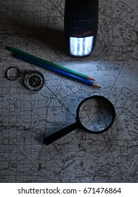 old military topographical map, pencil, luminous flashlight, mineral stone, magnifier and compass in the night