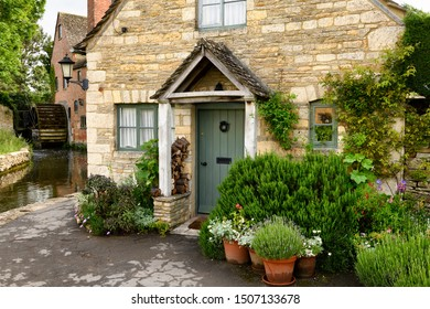 The Old Mill museum with undershot waterwheel on the River Eye with yellow Cotswold limestone house with potted plants Lower Slaughter, Cheltenham, England - June 16, 2019