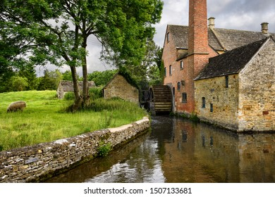 The Old Mill museum with undershot waterwheel on the River Eye with sheep Cotswold District Lower Slaughter, Cheltenham, England - June 16, 2019