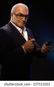 Old millionaire smoking cigar, using mobilephone, looking at camera.