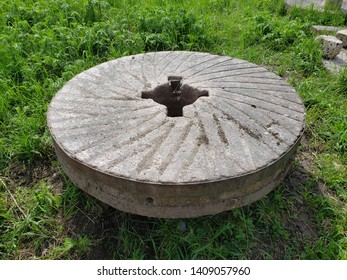 An old millstone laying on green grass. The stone is gray and weathered looking. It has grooves on its side and is heavily nicked from long-time use.