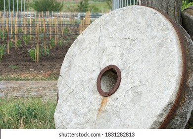 Old millstone for the mill. Large stone round millstone.