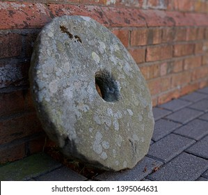 old millstone and red brick wall