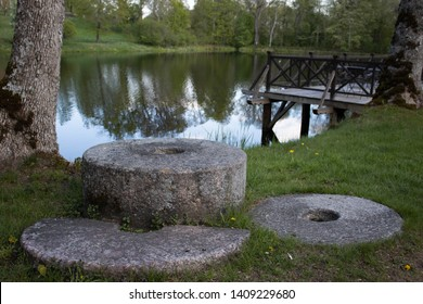 Old millstones lie on the grass near the river and wooden platforms. Close-up