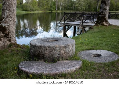 Old millstones lie on the grass near the river and wooden platforms.