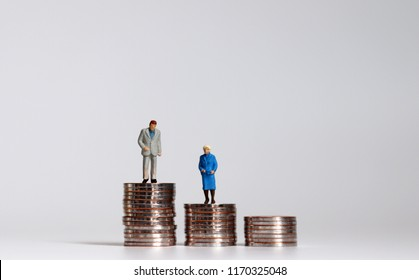 An old miniature man and woman standing on a pile of coins.