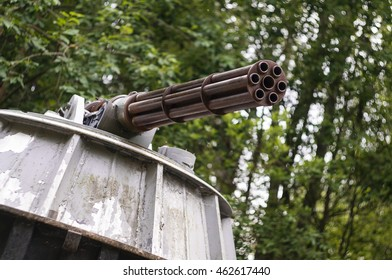 Old minigun on a stand in a forest.