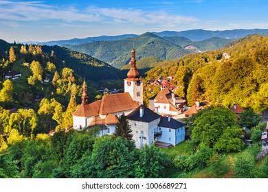 Old mining village and historic church in Spania dolina. Falltime trees at sunrise, Slovakia