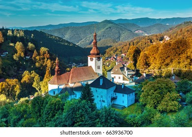 Old mining village. Historic church in Spania dolina. Falltime trees at sunrise,Slovakia