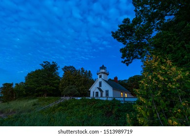 Old Mission Point Lighthouse at twilight showing lights in windows, at the 45th parallel on Old Mission Peninsula, Traverse City, Michigan.