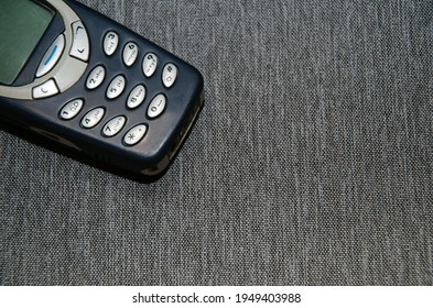 An old mobile phone on a rag-gray background.