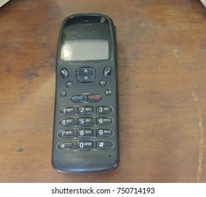 Old mobile phones with antenna isolated on wooden table.