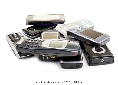 old mobile phones piled up on a table no people stock photo