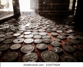 Old money coins collection behind window with sunlight in the background