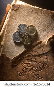 Old money. United Kingdom pre-decimal 1971 currency. Pounds, shillings and pence on old damaged bible book stamped with the  price, two shillings and six pence.