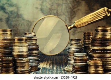 Old moneys and coins through a magnifying glass. Numismatics and collecting money.Russian Empire and world currency.Silver,gold.Searching for treasure concept.Vintage and retro style.
