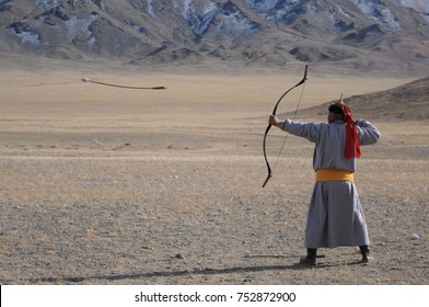 Old mongolian man competing in a n arrow and bow contest, during the golden eagle festival in the mountains countryside of Mongolia