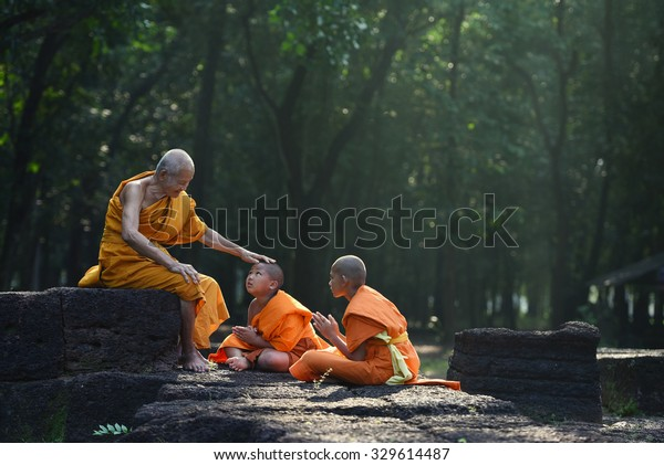 Old Monk are teach little monks of buddhist and spiritual ancient buddha on the laterite in the forest