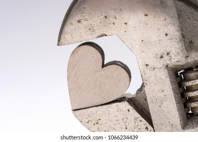 Old monkey wrench and wooden heart isolated