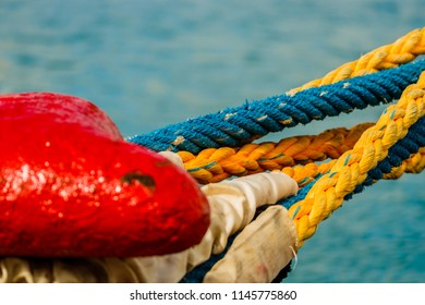 Old mooring bollard with heavy ropes in the port of Saint Lucia. Mooring end of a rope anchoring a ship.