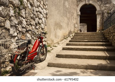 An old moped parked between the stone steps and the city walls