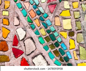 Old mosaic on the wall with fragments of yellow, green, emerald, marsh, gold, orange, brown, turquoise colors in places with fallen and broken mosaic particles on the background of pinkish cement