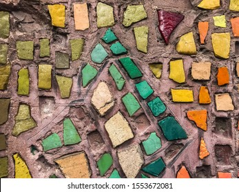 Old mosaic on the wall with fragments of yellow, green,red, emerald, marsh, gold, orange, brown, turquoise colors in places with fallen and broken mosaic particles on the background of pinkish cement