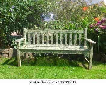 Old mossy wooden park bench, in Grouville, Jersey